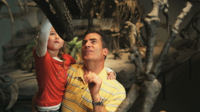 MS Farther with daughter (8-9) and son (10-11) looking at dinosaurs skeleton in natural history museum, Lehi, Utah, USA