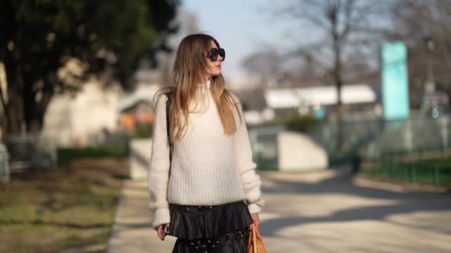 "fashion blogger ""mascarada paris"" wears sunglasses, a white wool pullover, a black ruffled skirt, an orange bag, shoes, outside elie saab, during... - paris fashion week - haute couture spring/summer 2020点の映像素材/bロール"