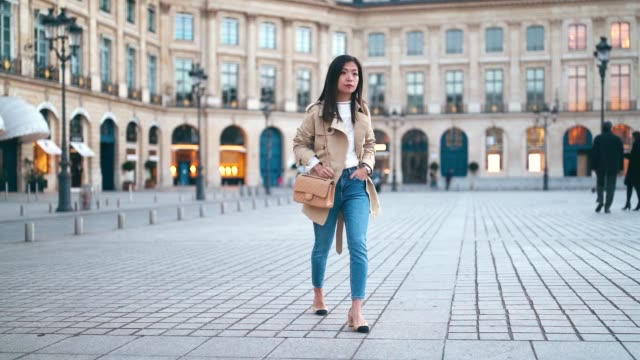 vídeos de stock e filmes b-roll de fashion blogger maymaryb wears a beige trench coat a white top a chanel bag blue denim jeans slingback shoes on march 16 2019 in paris france - sapato aberto atrás