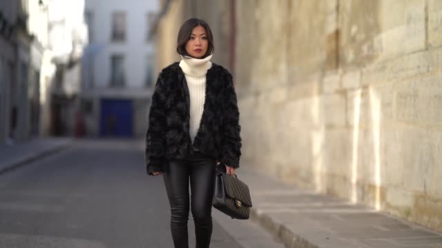 Fashion blogger Maymaryb wears a black fur coat a white turtleneck wool pull over a Chanel jumbo bag black leather pants black shoes during Paris...