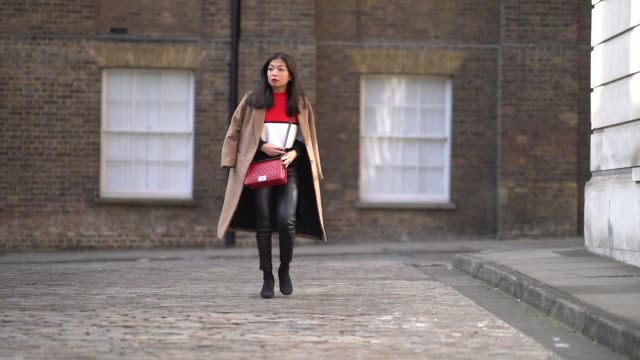 fashion blogger maymaryb wears a red chanel boy bag a camel coat a red white and black pull over black leather pants black shoes during london... - london fashion week stock videos and b-roll footage
