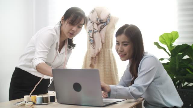 fashion clothing designer working together on laptop - designer clothing stock videos & royalty-free footage