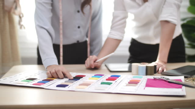fashion clothing designer working together on pantone color chart - designer clothing stock videos & royalty-free footage