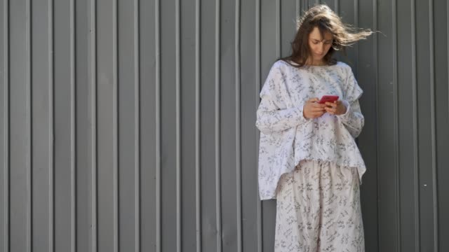 fashion concepts. young woman using technology in front of grey background - fashion week stock videos & royalty-free footage