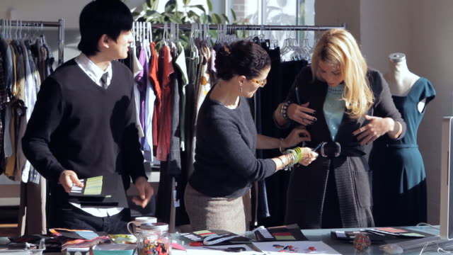 MS Fashion designer and assistants discussing on swatch colors / New York City, New York, USA