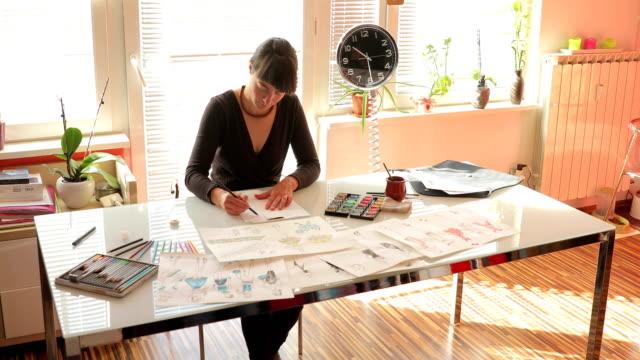 vídeos de stock, filmes e b-roll de designer de moda desenho ideias em esboços - estilista de moda designer profissional