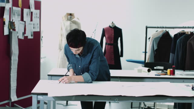 fashion designer drawing in studio - atelier stock-videos und b-roll-filmmaterial