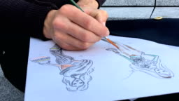 Fashion Designer Drawing Sketches Outdoors in a City