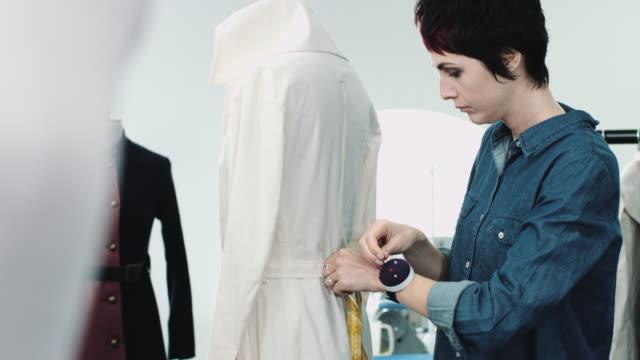 fashion designer dressing mannequin fashion model in studio - トルソー点の映像素材/bロール