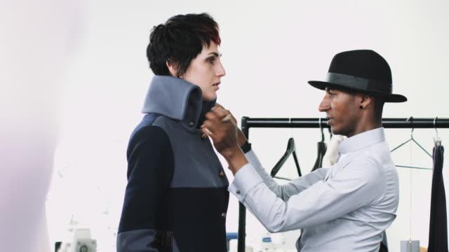 Fashion designer dressing mannequin fashion model in studio