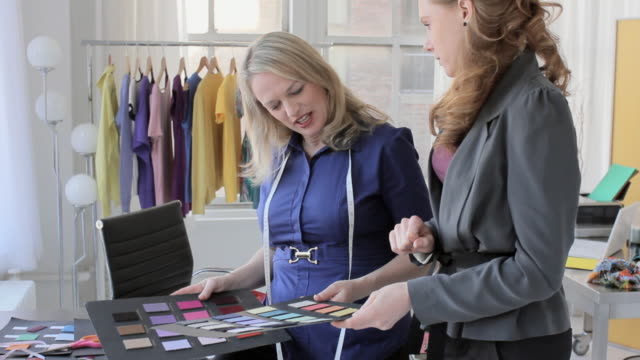 ms fashion designer in her studio looking at color swatches with assistant / new york city, new york, usa - designer video stock e b–roll