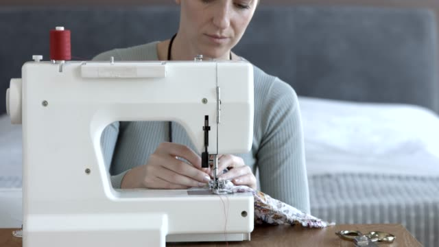 fashion designer sewing textile on machine at home - sewing stock videos & royalty-free footage