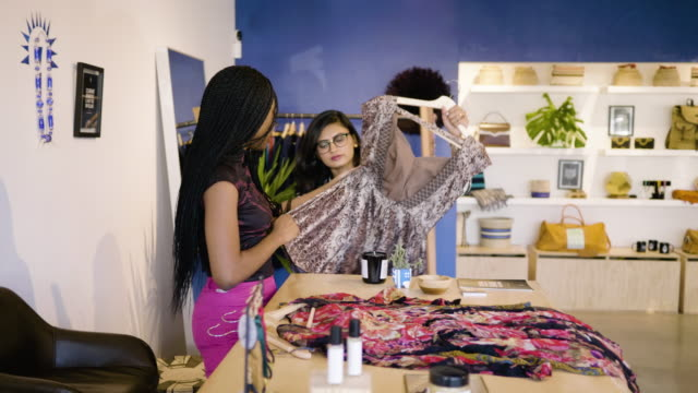 a fashion designer shows her clothing samples to a boutique owner. - camicetta video stock e b–roll