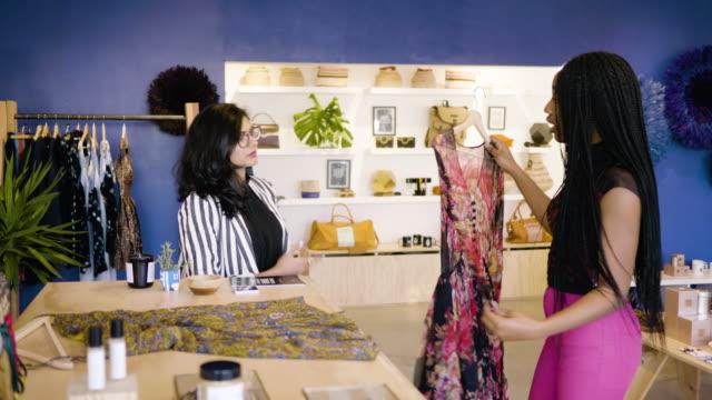 vídeos y material grabado en eventos de stock de a fashion designer shows her clothing samples to a boutique owner. - vestimenta para mujer