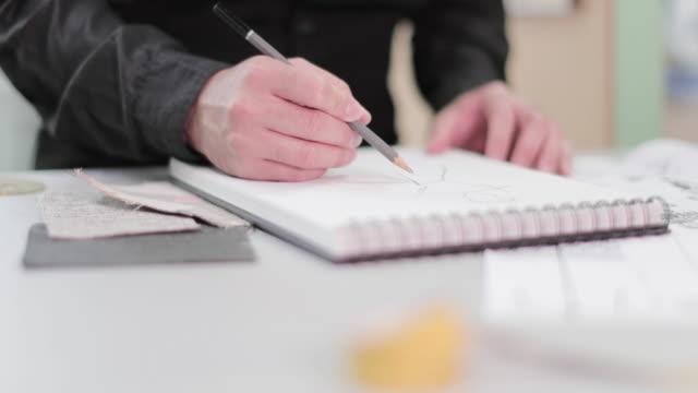 stockvideo's en b-roll-footage met fashion designer sketching a design - designatelier
