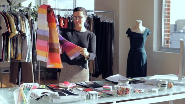 MS Fashion designer sorting through fabric swatches at desk / New York City, New York, USA