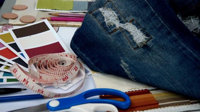 vidéos et rushes de styliste studio avec jean bleu déchiré et équipements concept commercial de vêtement - jeans texture