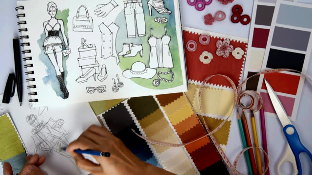 Fashion designer & Tailor drawing and working with sketch of clothes, samples/ garment business concept