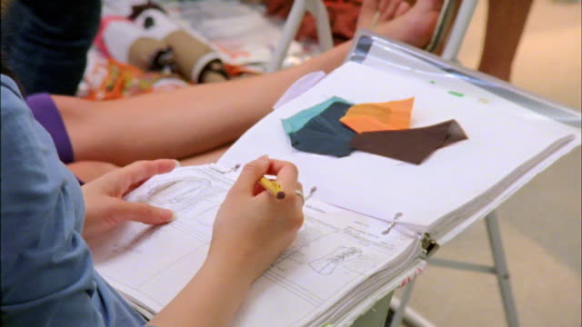 cu fashion designer taking notes on fit session, new york city, new york, usa - 生地サンプル点の映像素材/bロール