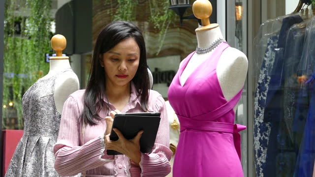 fashion designer using tablet while measuring dress on mannequin at clothing store - fashion designer stock videos & royalty-free footage