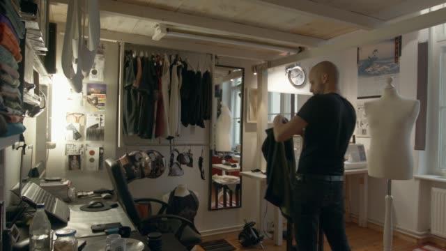 fashion designer wearing new garment in front of the mirror - ジャケット点の映像素材/bロール
