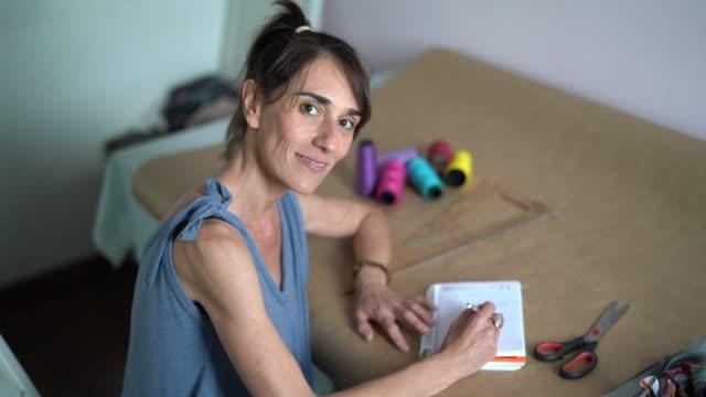 vídeos y material grabado en eventos de stock de diseñador de moda mujer que trabaja en casa - retrato de la pequeña empresa - adulto de mediana edad