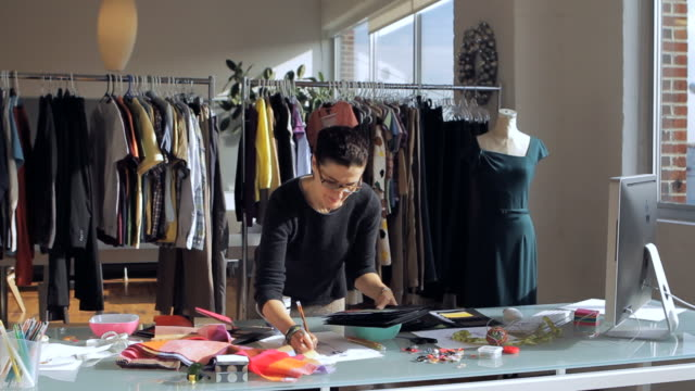 ms fashion designer working at desk while looking at swatch board / new york city, new york, usa - fashion designer stock videos and b-roll footage
