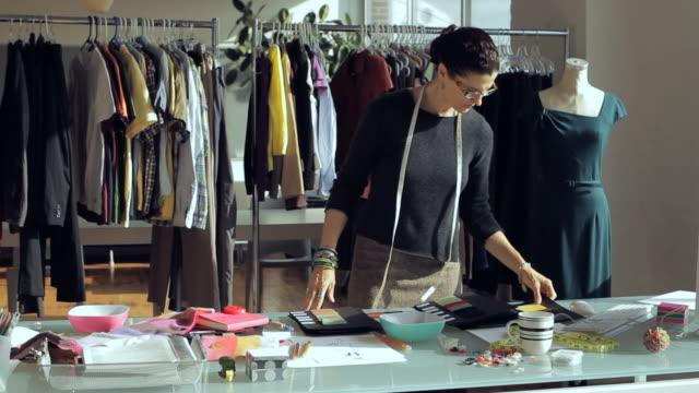 MS TD PAN Fashion designer working at desk while sorting through clothing racks/ New York City, New York, USA