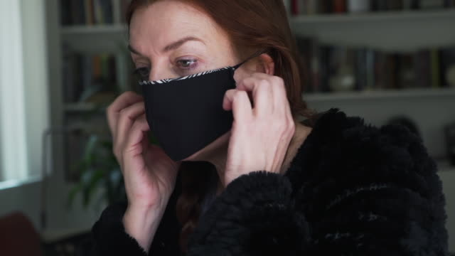 fashion designer working at home creates face masks from recycled fabric as protection against  viruses, disease and germs - sewing machine stock videos & royalty-free footage