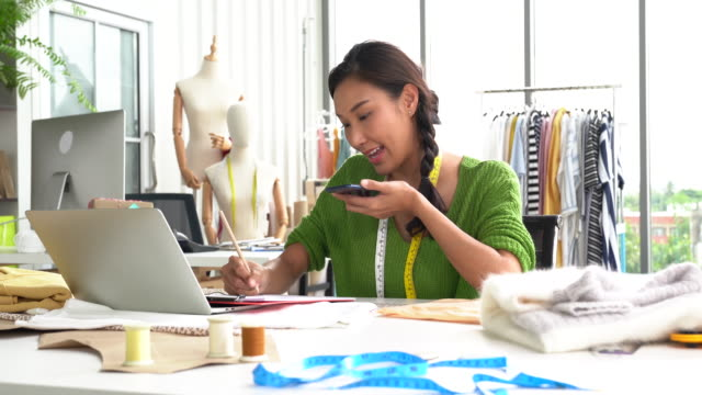 fashion designer working in the studio and on the phone with a client - tailored clothing stock videos & royalty-free footage