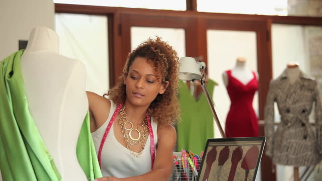 ms pan fashion designer working on dress form using mannequin and laptop in design studio / richmond, virginia, usa - fashion designer stock videos and b-roll footage