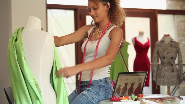 ms tu pan fashion designer working on dress form using mannequin and laptop in design studio / richmond, virginia, usa - fashion designer stock videos & royalty-free footage