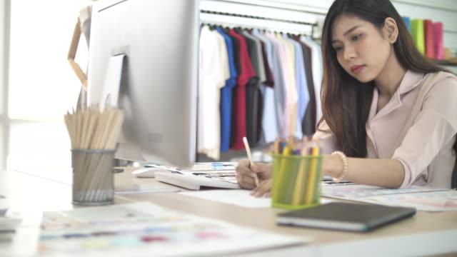コンピュータでスケッチを操作するファッションデザイナー - 生地サンプル点の映像素材/bロール