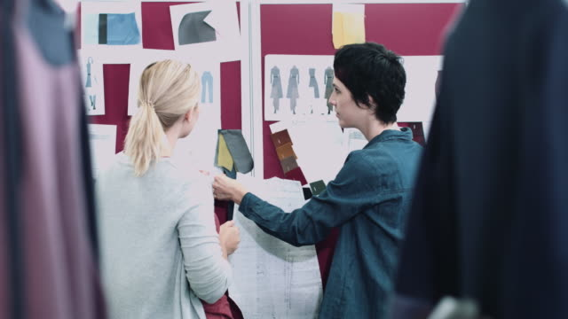 Fashion designers looking at designs in studio