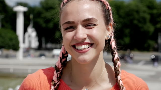 Fashion girl with brown eyes and hair in pigtails smiling at the camera