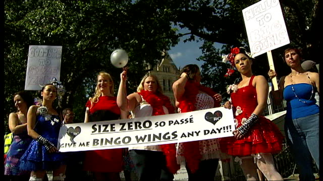 london fashion week 2008 ext banners advertising london fashion week group of women wearing tutus demonstrating against size zero models - ballettröckchen stock-videos und b-roll-filmmaterial