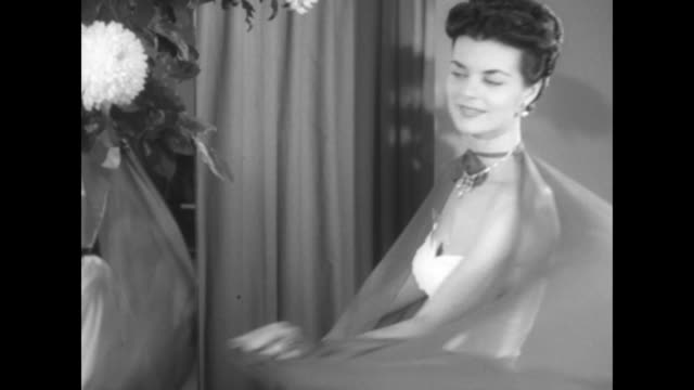 vidéos et rushes de vs fashion model displaying evening gown and chiffon stole she is wearing to people sitting in room - châle