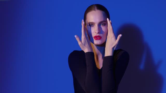 modemodel in schwarzem body berührt ihr gesicht mit ihren händen. - mascara stock-videos und b-roll-filmmaterial