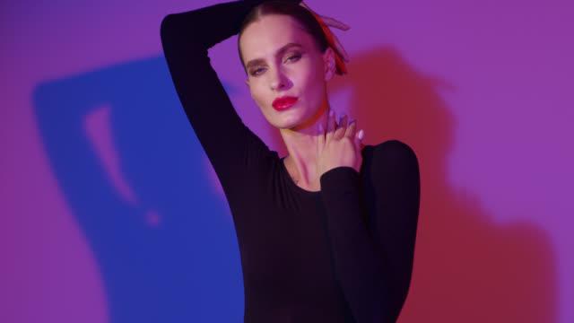 modemodel in schwarzem body berührt ihr gesicht mit ihren händen. - mund stock-videos und b-roll-filmmaterial