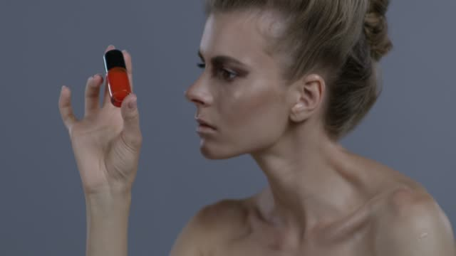 fashion model handles a bottle of the red nail polish. fashion video. - neck stock videos & royalty-free footage
