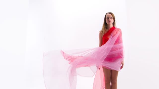Fashion model in bikini with flowing red fabric