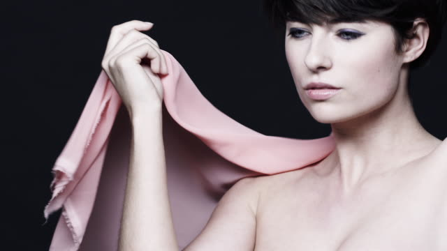 A fashion model  poses with a pink shawl at a photo shoot in Germany.