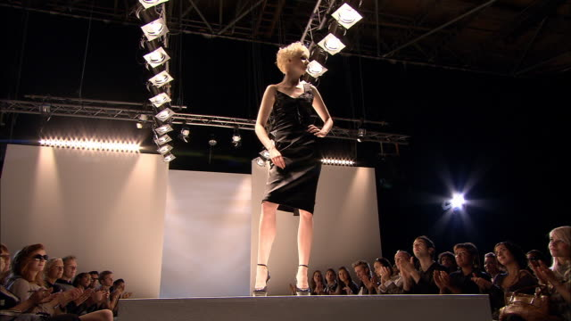 LA WS Fashion model posing on catwalk at fashion show as audience claps and photos are taken of her/ London, England