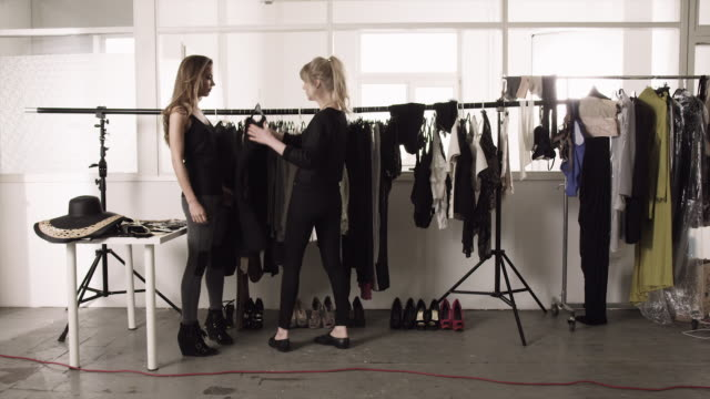 A fashion model selects clothes from a rack in a dressing room in Germany.