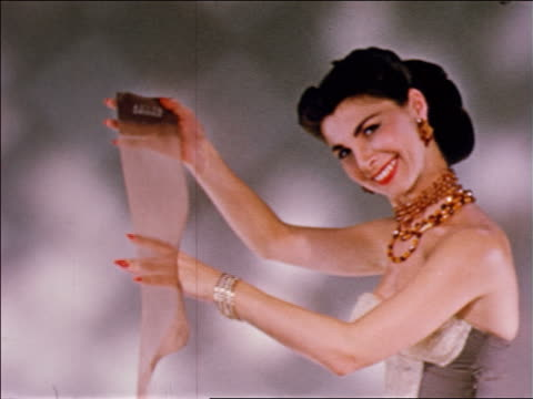 vídeos de stock e filmes b-roll de 1956 fashion model smiling + holding stocking in studio / industrial - meia calça