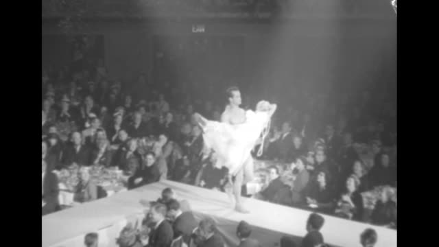 Fashion model wearing cover over bathing suit walks down runway man wearing swimming trunks walking behind her man picks woman up and carries her to...