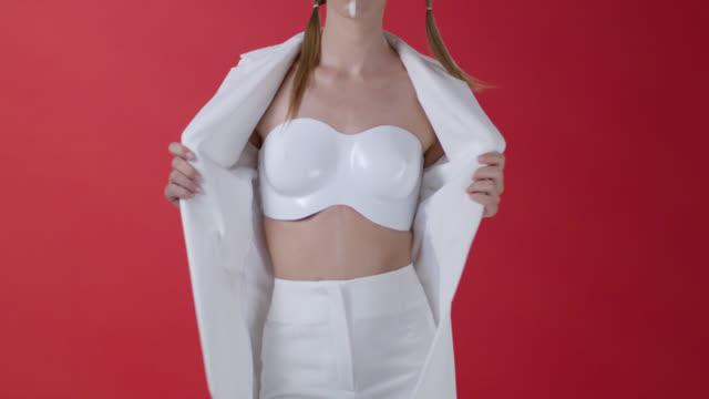 Fashion model`s body. Girl wearing  white jacket shows plastic bra. Fashion video.