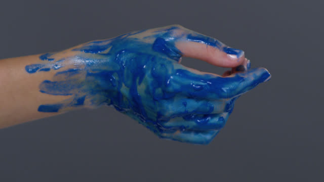 Fashion model`s hand painted blue. Fashion Video.