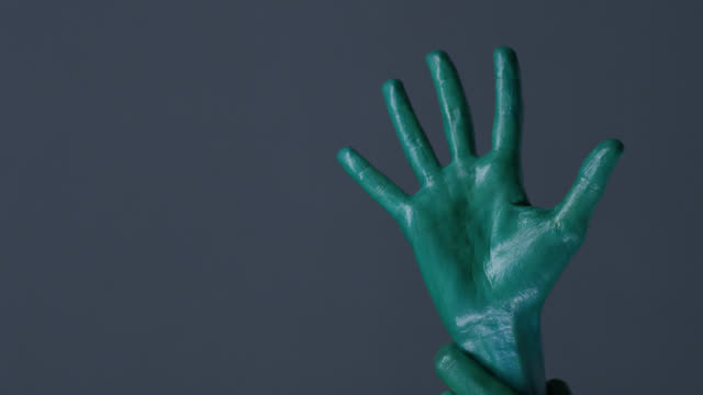 Fashion model`s hands painted green shows gestures. Fashion Video.