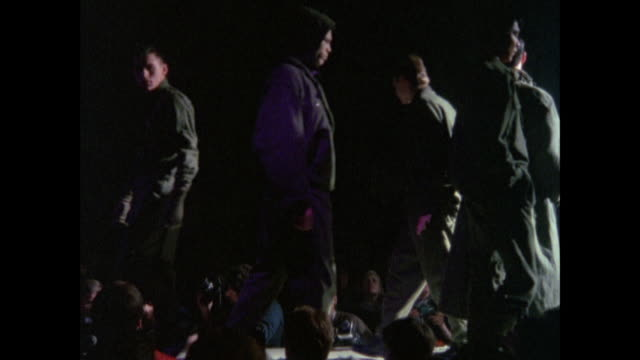 MONTAGE Fashion models parading down a dimly lit runway / London, England, United Kingdom
